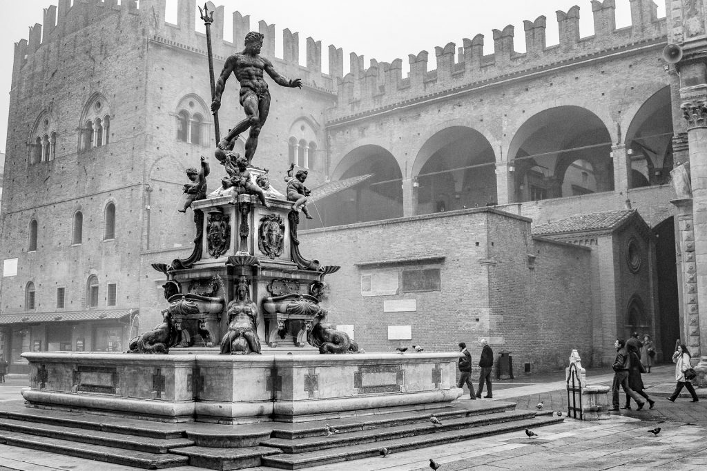 Statue of Neptune in Bologna, in front of the castle with passers by on a misty autumn morning. Just the topic to start critiquing images.