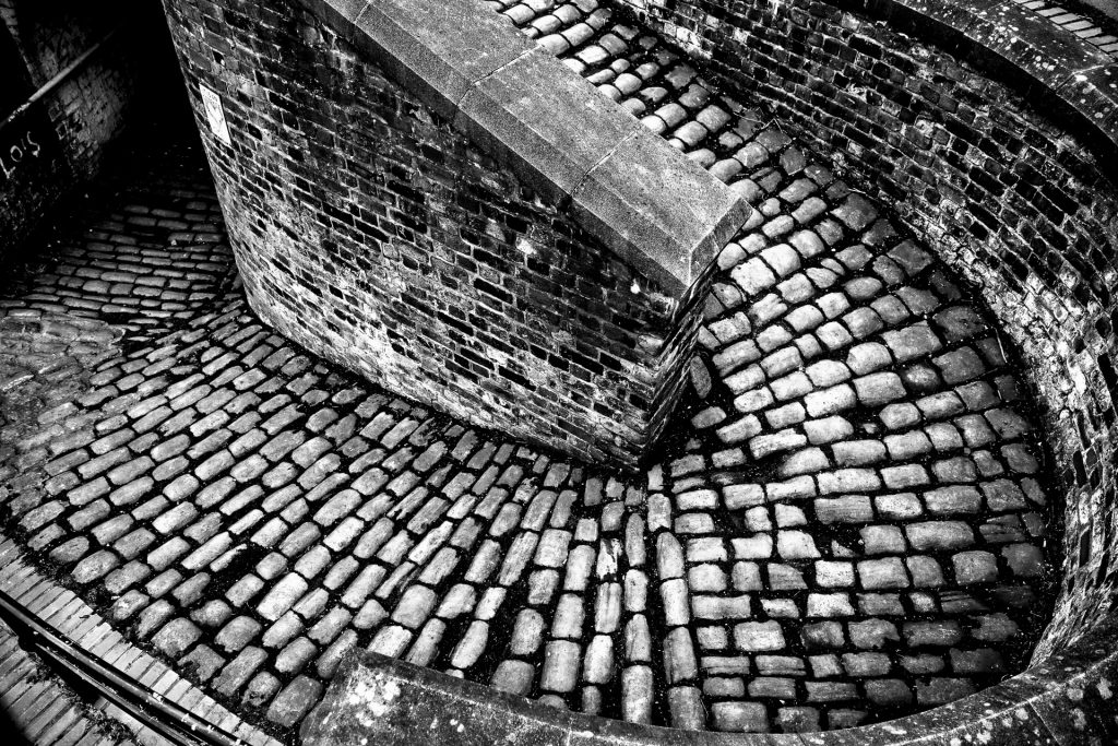 Ancoats Canal Bridge, Manchester. Cobbled spiral ramp leading to a dark dark tunnel