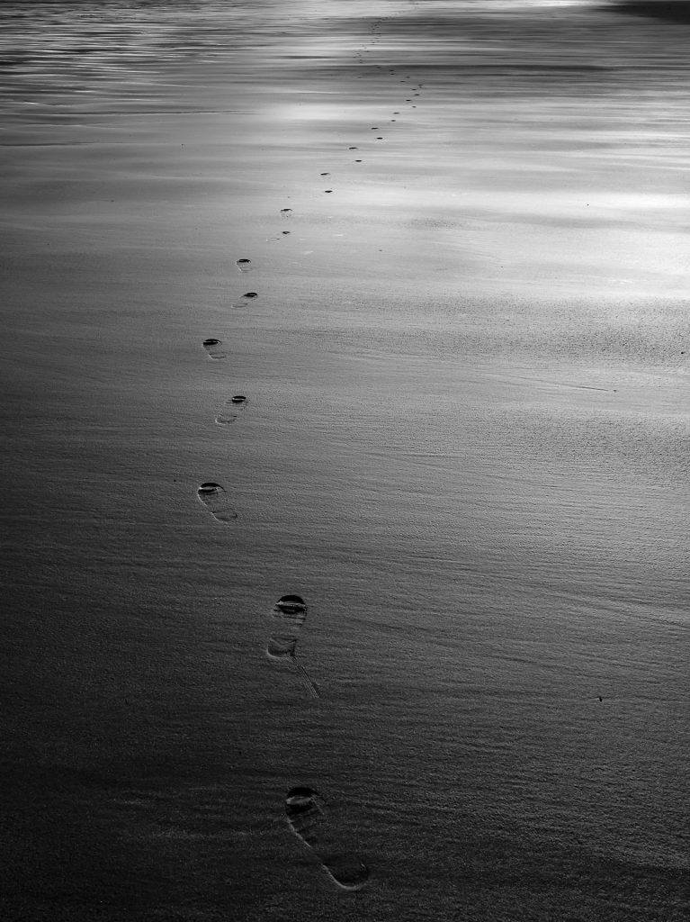 Footprints across a beach leading to an uncertain destination
